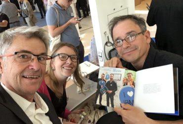 Universités IBM i 2018 avec le livret « IBM i 30th Birthday » diffusé mondialement et présentant l'équipe KUHN sur notre stand ITHEIS en page 3